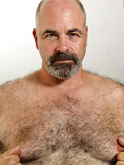 Hairy daddy Tony Thompson strokes his fat uncut dick